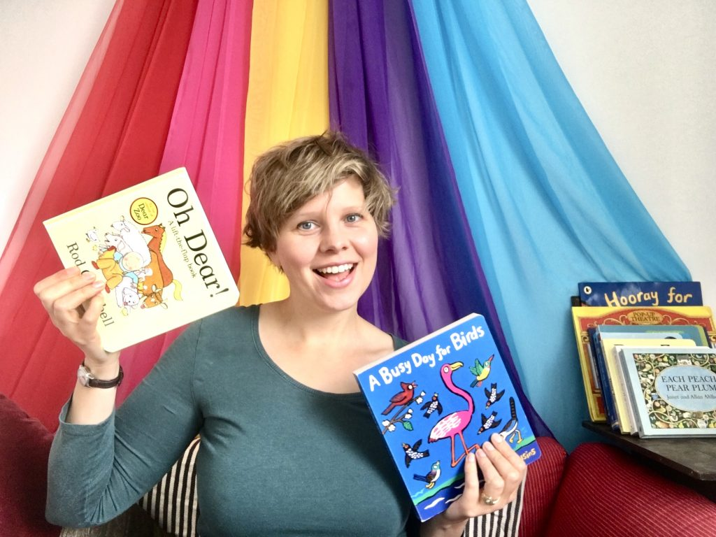 Woman smiling and holding children's books
