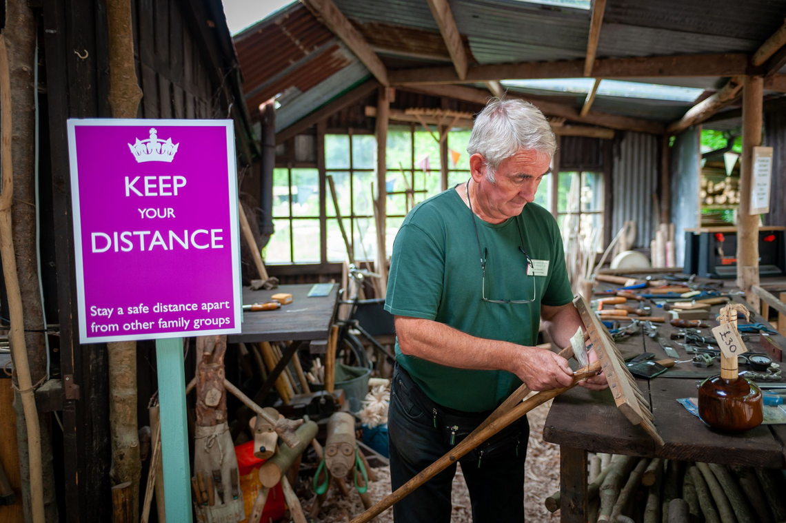 A volunteer at Amberley Museum next to a Keep your Distance sign