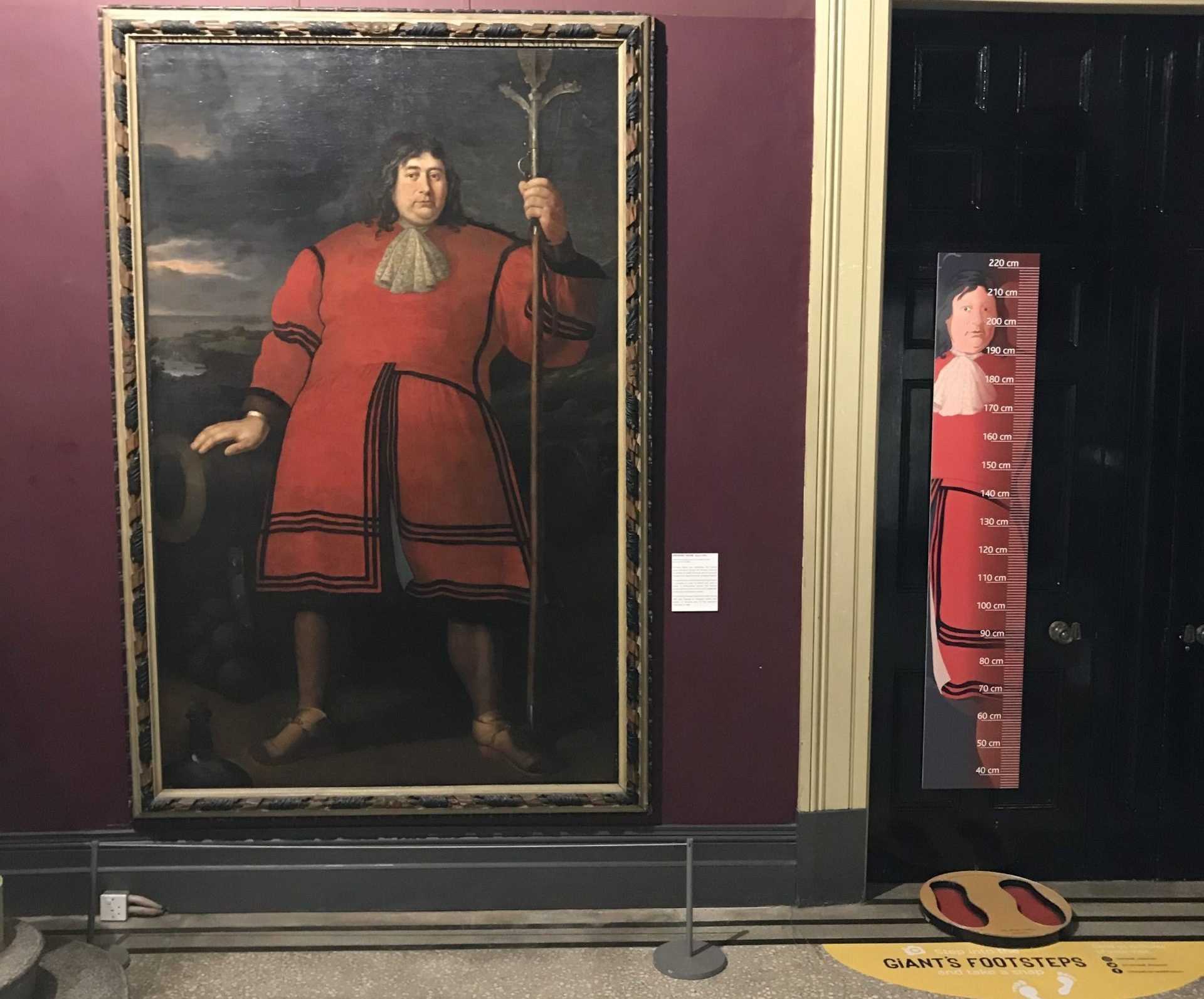 Portrait of Anthony Payne, alongside an interactive that allows visitors to compare their height and feet size