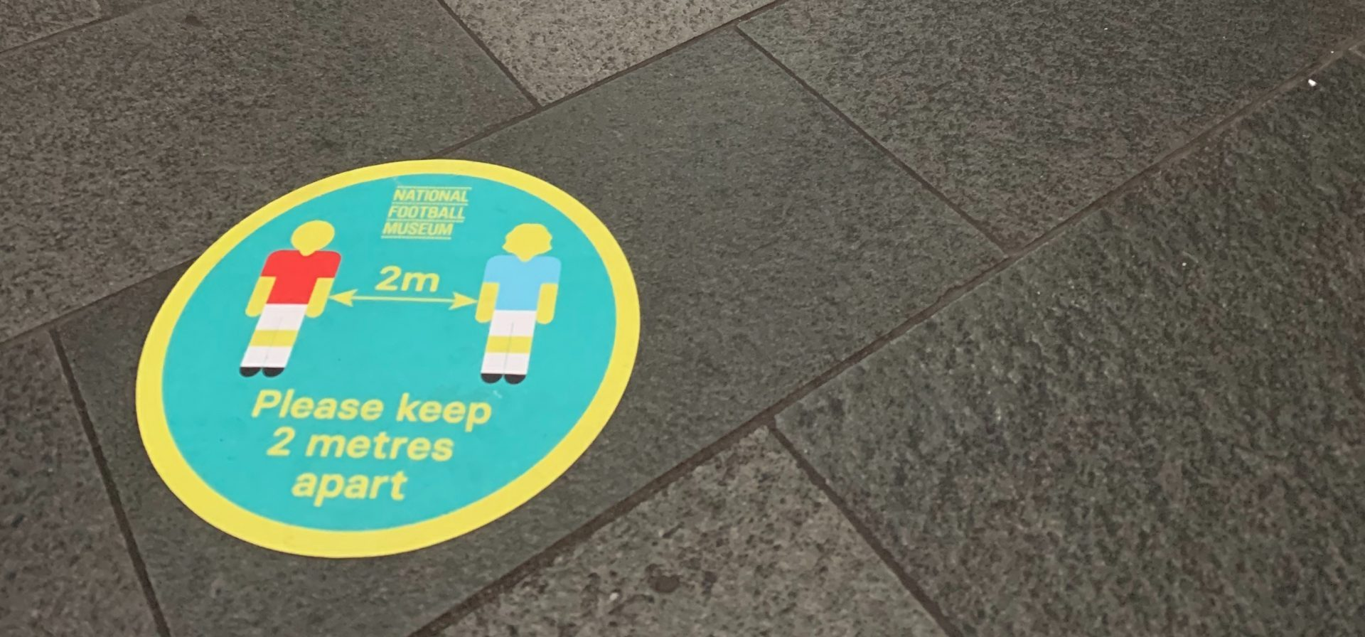 A floor sticker reminding people to keep their distance at the National Football Museum