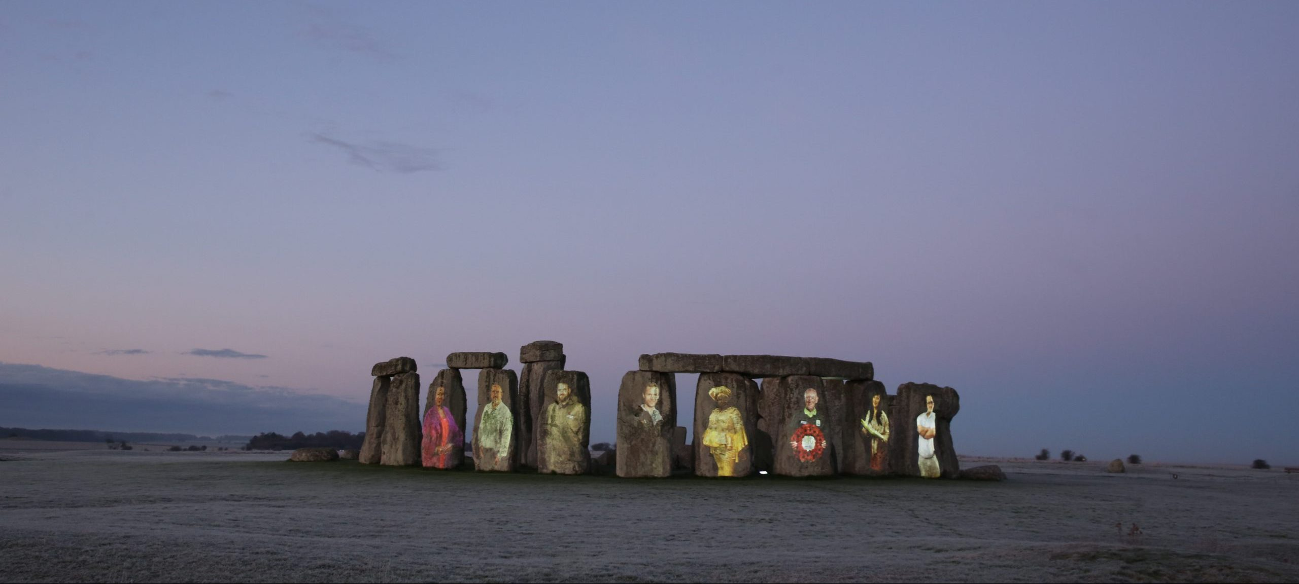 Stonehenge at dawn, illuminated with projections of eight unsung heroes of heritage