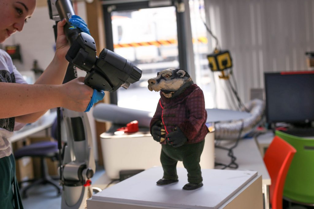 A woman digitally scans a model of a badger