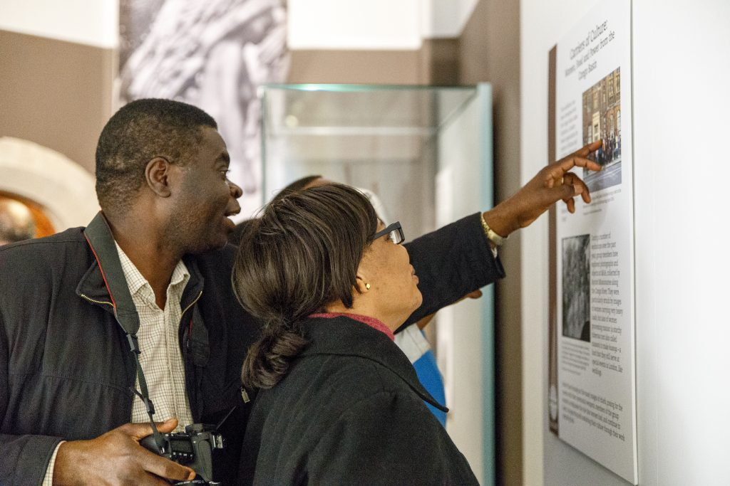 A man and a woman look at some text on a wall of an exhibit