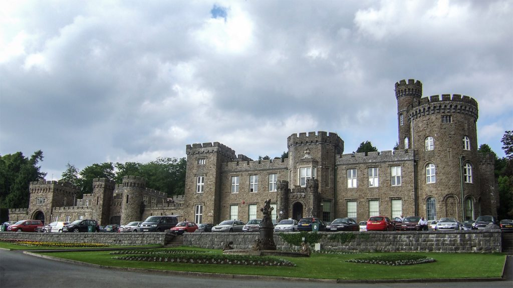 The front exterior of Cyfarthfa Castle, with cars parked in front