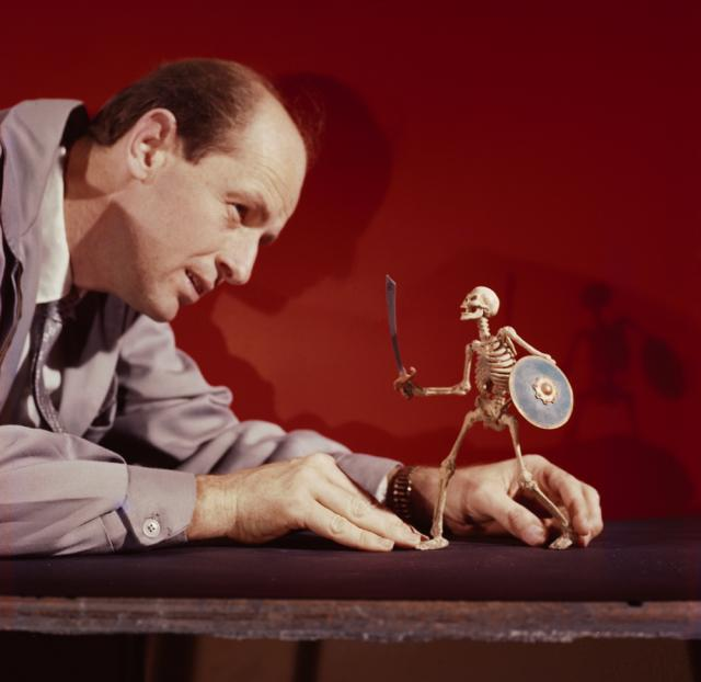 A man holds a small figurine skeleton