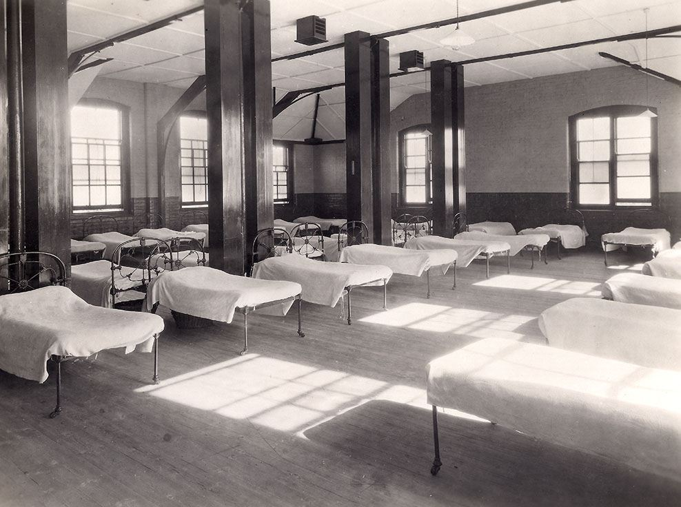 A black and white picture of a ward in the Foundling Hospital, Redhill. Multiple beds are lined uniformly in rows all of them have the same white sheets.