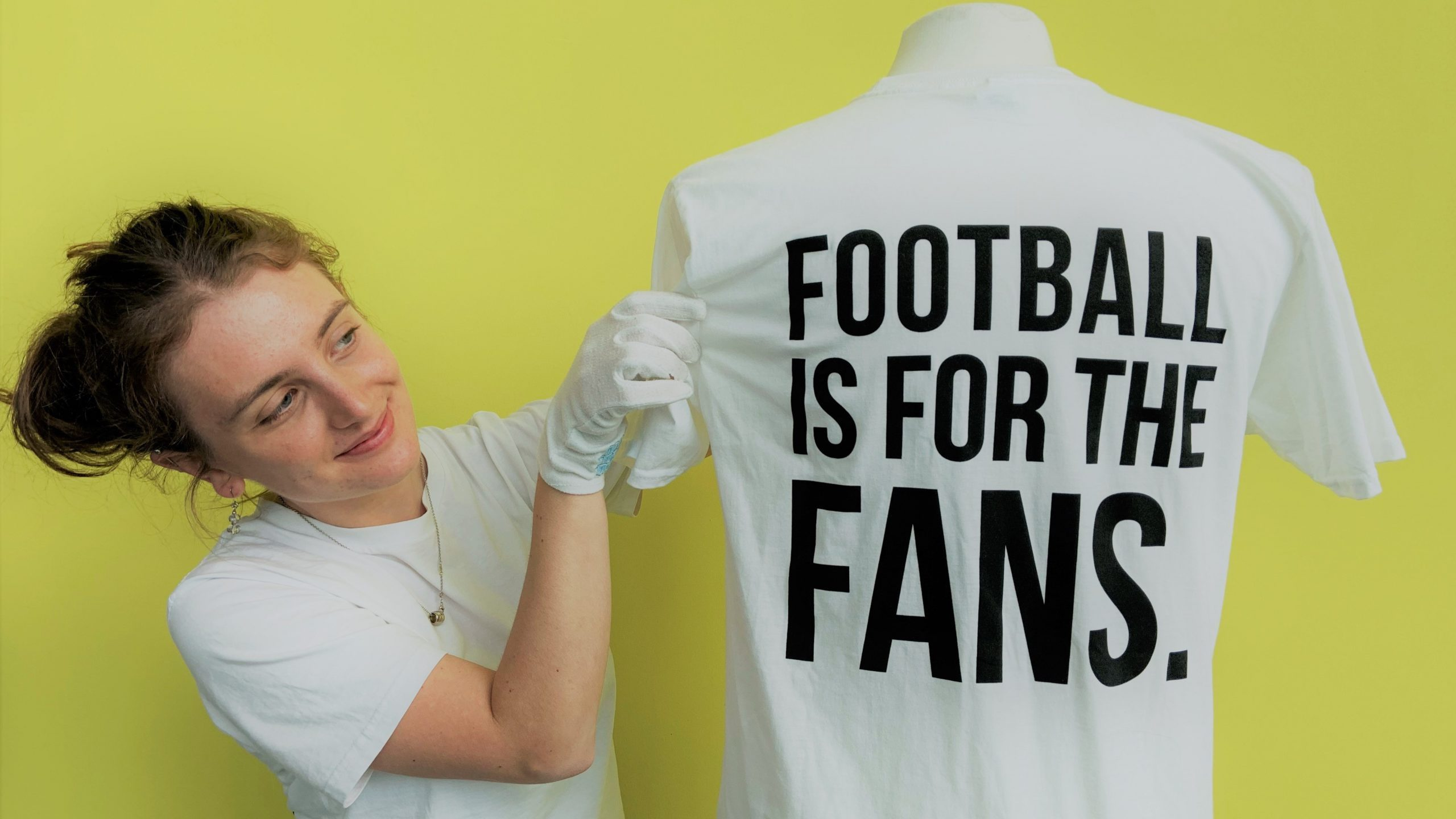 Tilly Johnson, a Museum Futures trainee at the National Football Museum, with the 'Earn It/Football Is For the Fans' T-shirt