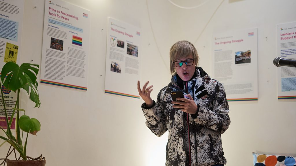 A person speaking at the Peace Museum with LGBT-themed displays