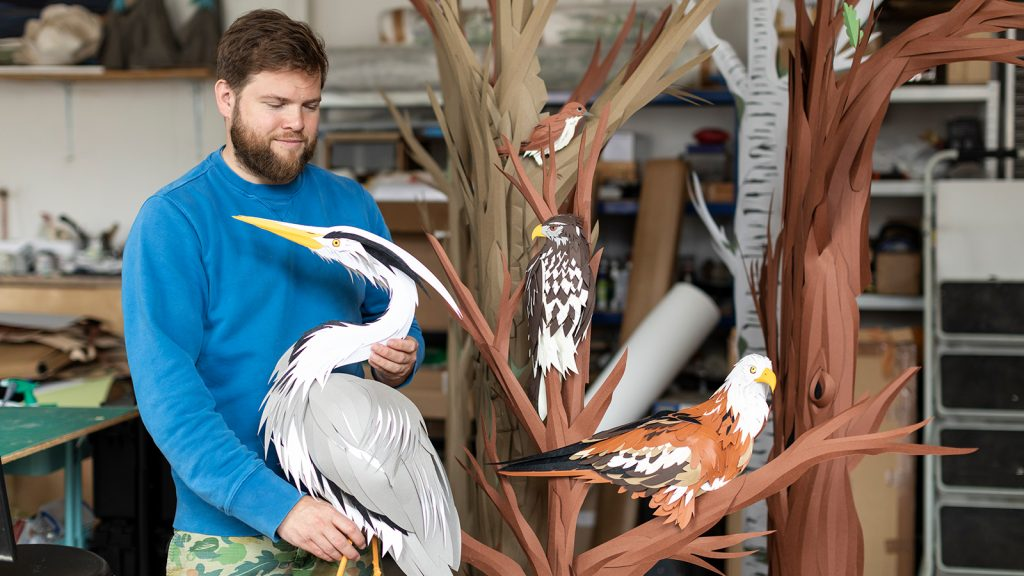 Andy Singleton holding a model of a bird