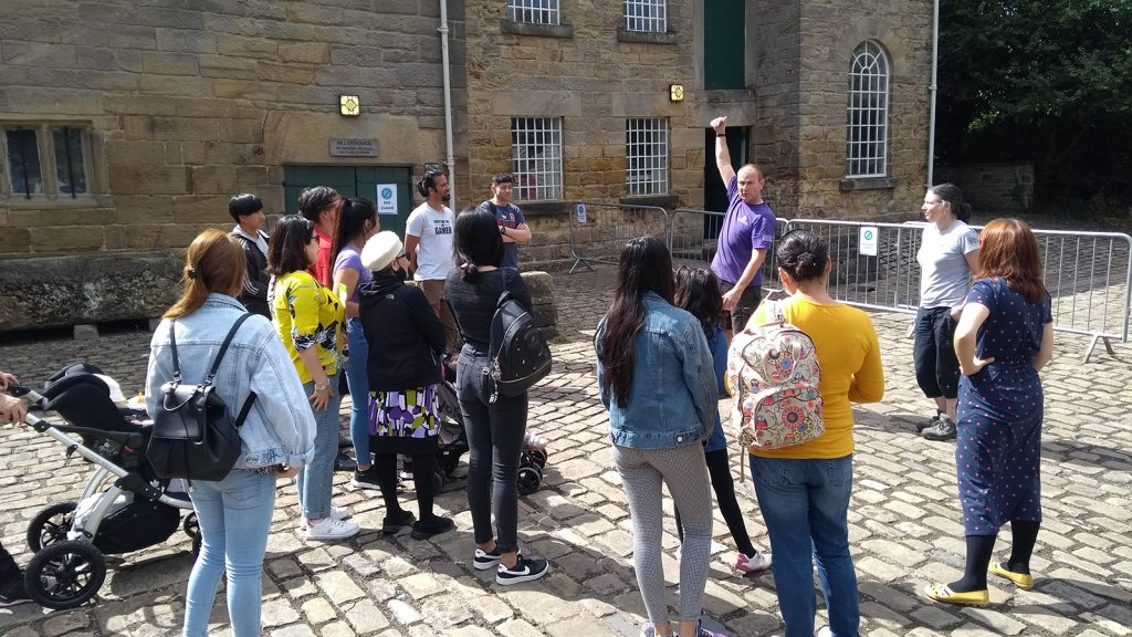 A group gathers to listen to a guide at Barnsley Museum