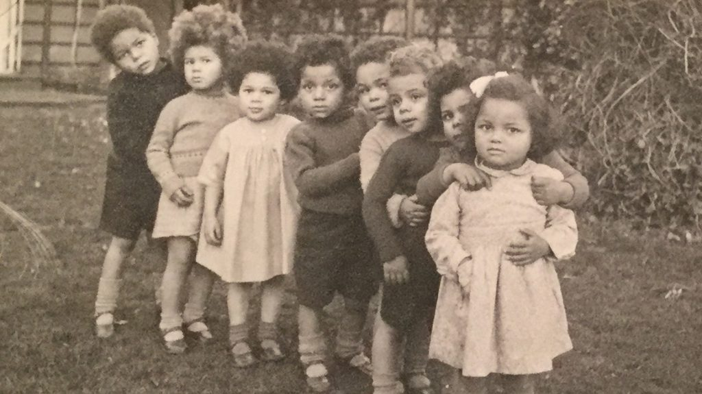 A sepia photo of young children standing in a line