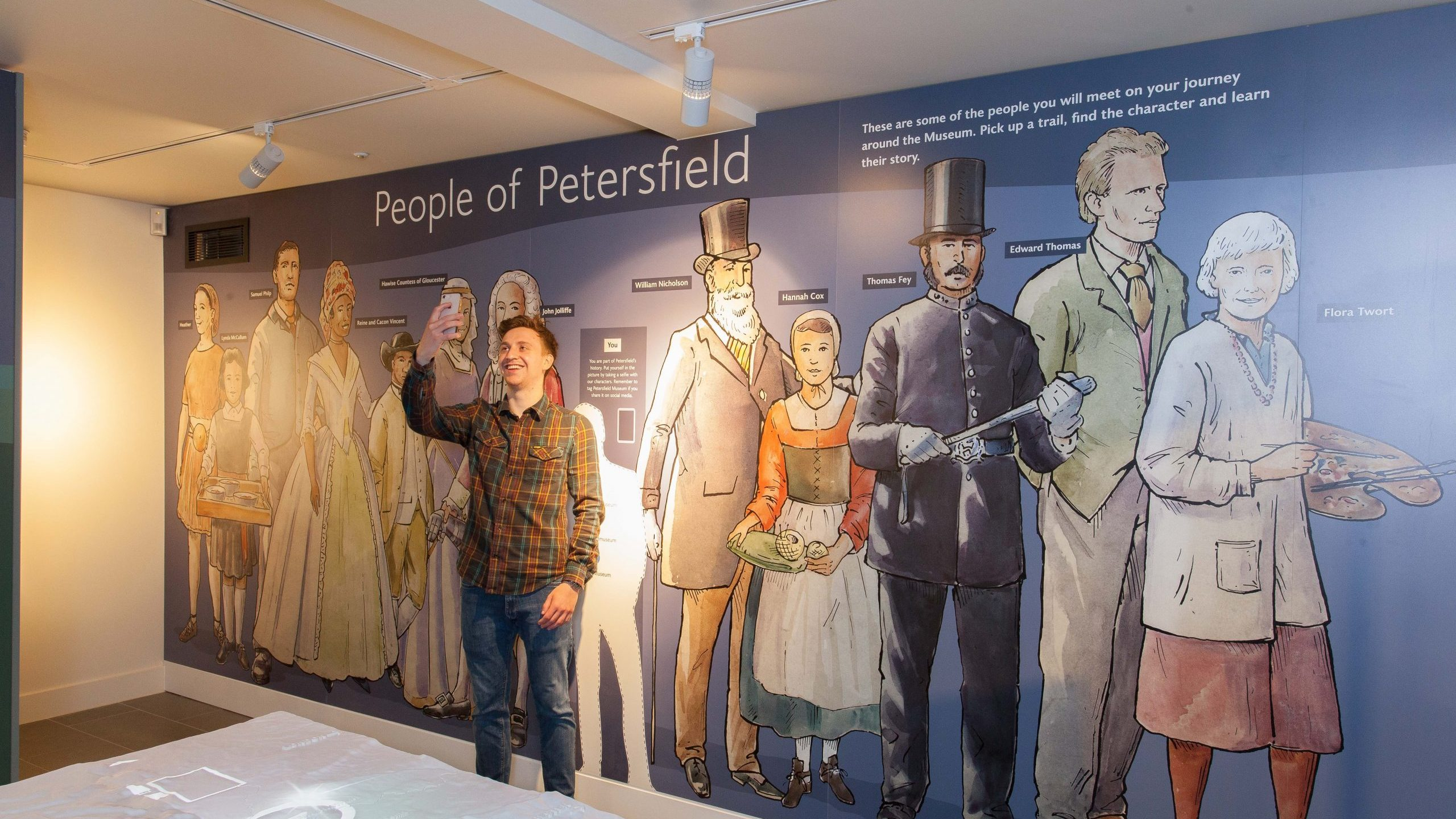 A visitor taking a selfie with a mural of some of the people of Petersfield, including artist Flora Twort and poet Edward Thomas