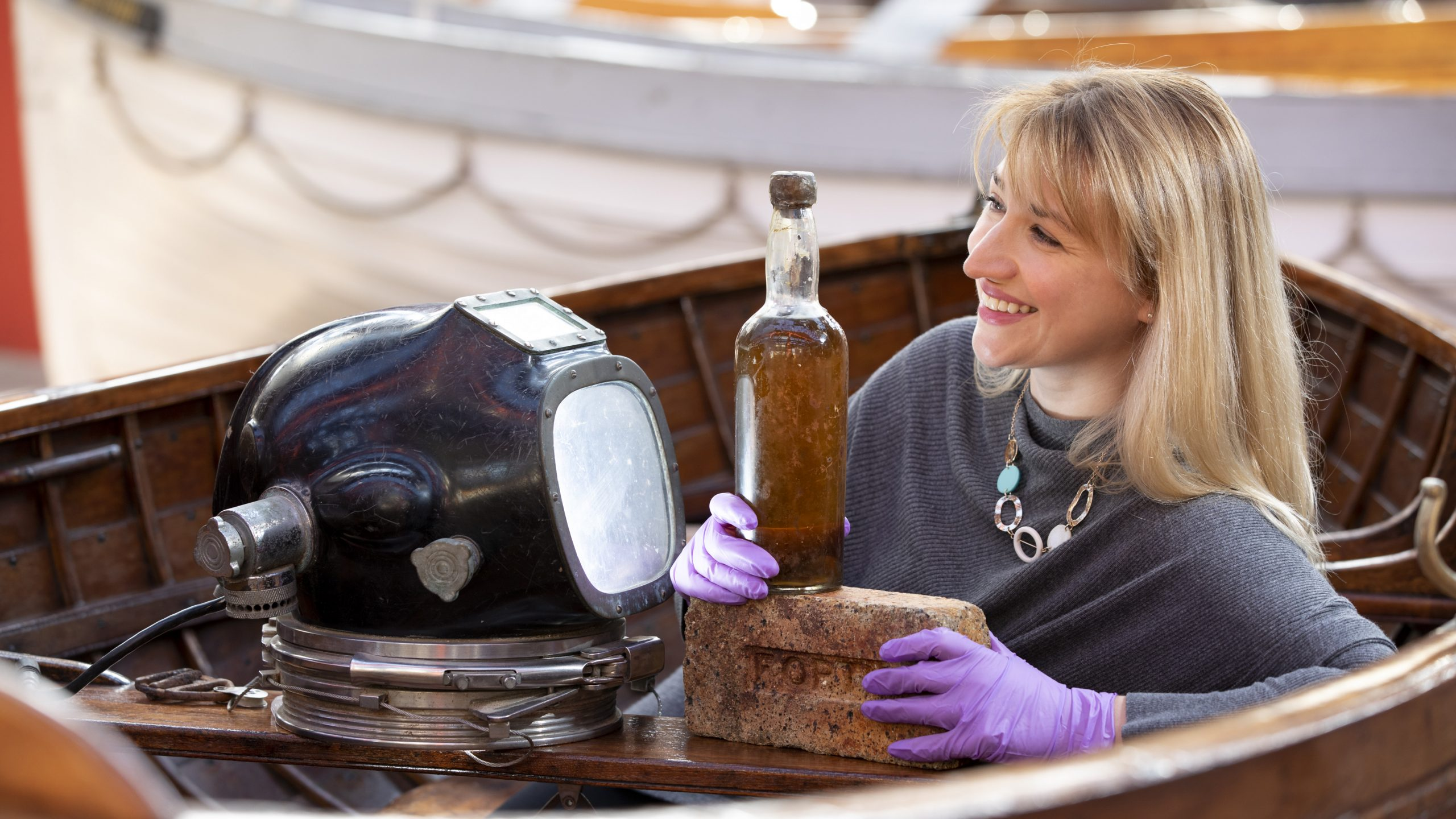 Abigail McIntyre, senior curator at the Scottish Maritime Museum, pictured with an 80-year-old bottle of Scottish whisky salvaged from the 1923 SS Politician