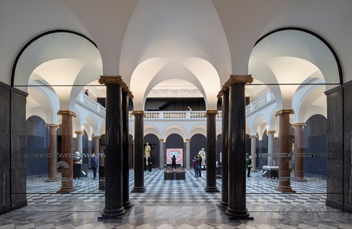 A view of the gallery interior with black columns and white ceiling