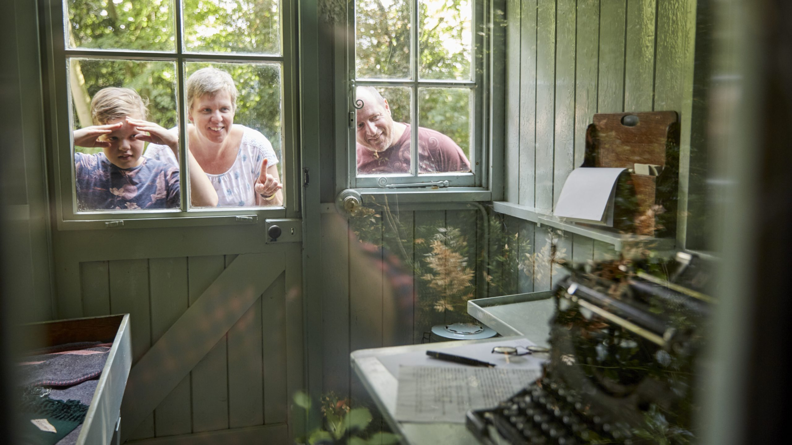 Visitors Looking Inside The Writing Shed At Shaw's Corner, Hertfordshire